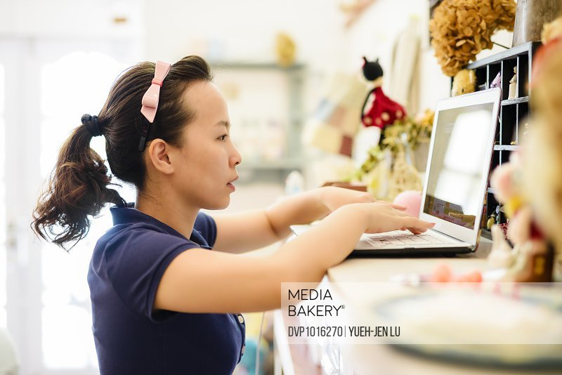 Young woman using laptop standing