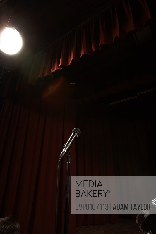 Microphone on empty stage lit by spotlight