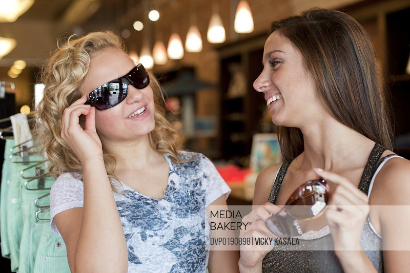 Teen girls shopping for sun glasses at boutique