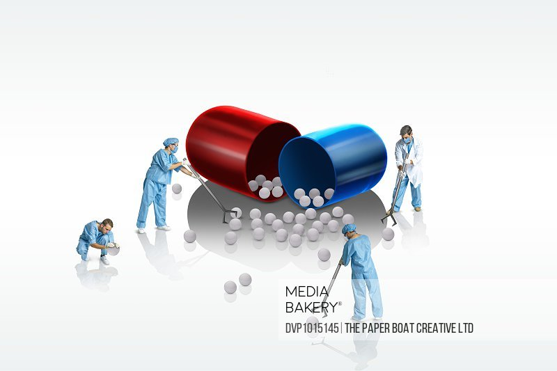 scientists picking up parts of a large pill