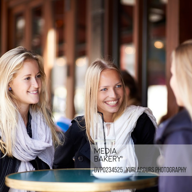 Three friends seated at a coffee shop talking to each other and smiling