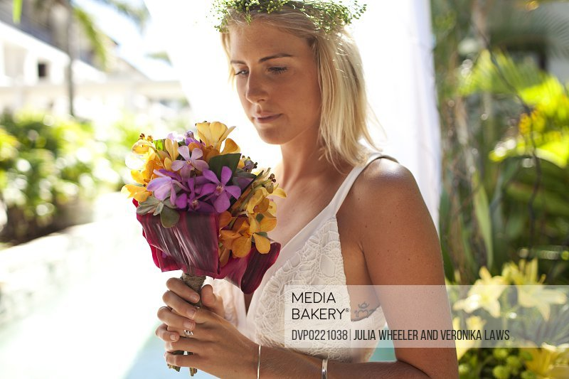 Bride holding tropical flowers