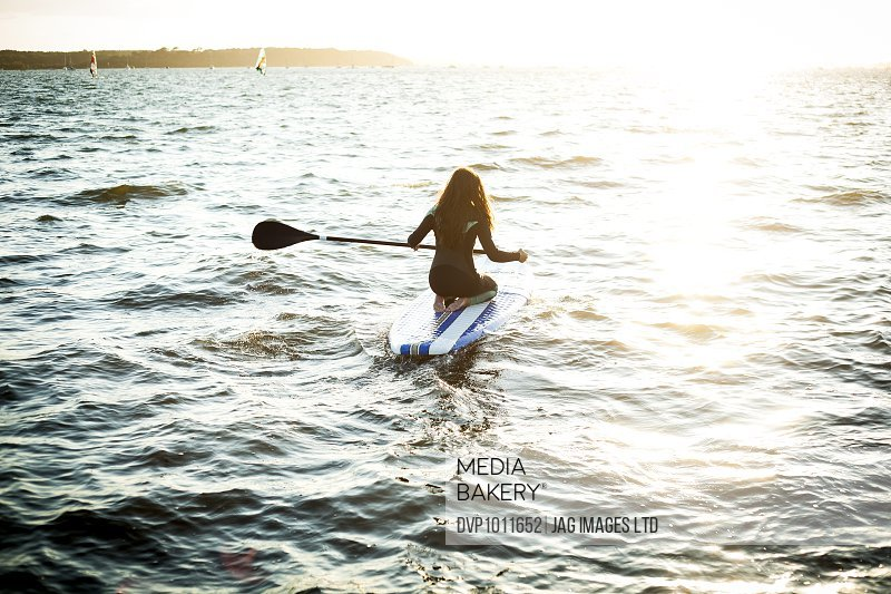 young woman paddle boarding at sunset