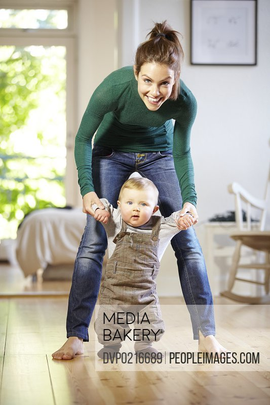 Smiling young mom helping her baby boy learn to walk