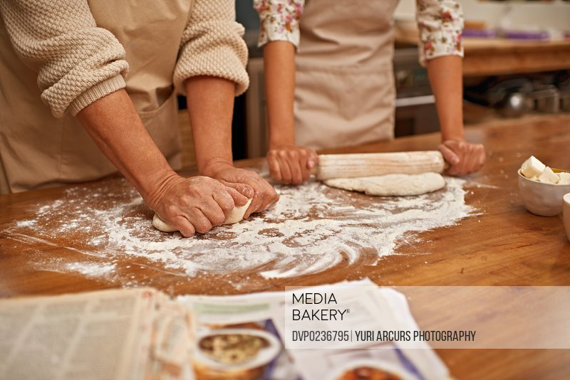 A cropped view of hands working the dough while baking in a kitchen