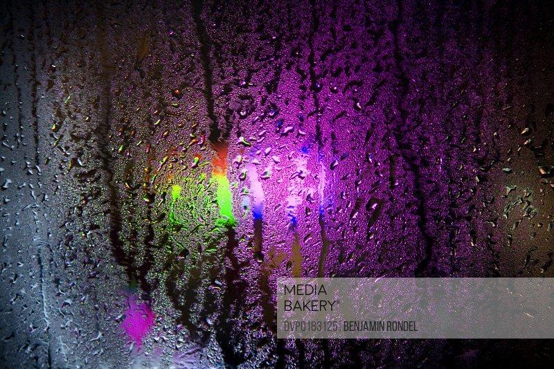 Colored lights inside room seen through wet window
