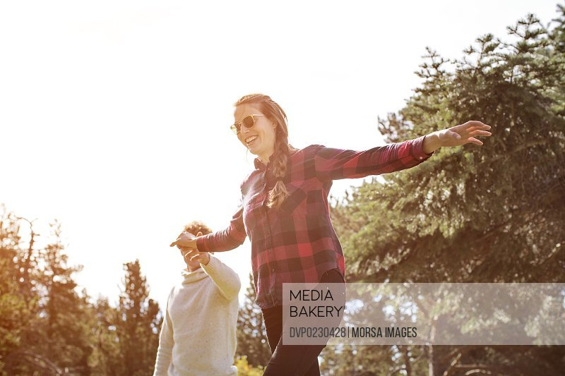 Man assisting woman to walk on slack-line
