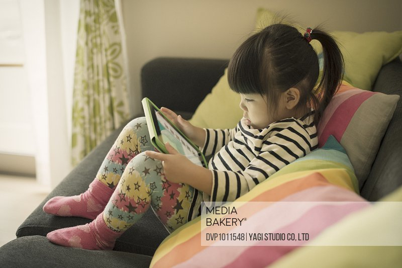 The girl using a digital tablet on sofa