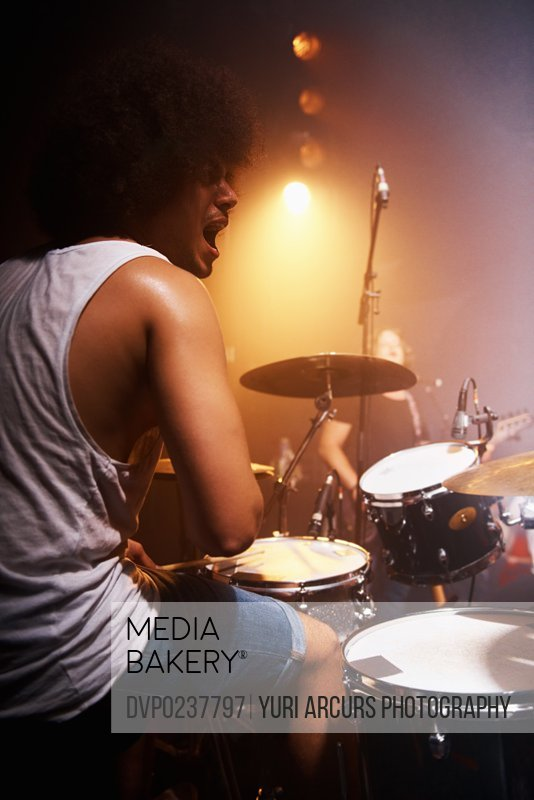 Shot of a talented drummer playing drums at a concert. This concert was created for the sole purpose of this photo shoot, featuring 300 models and 3 live bands. All people in this shoot are model released.