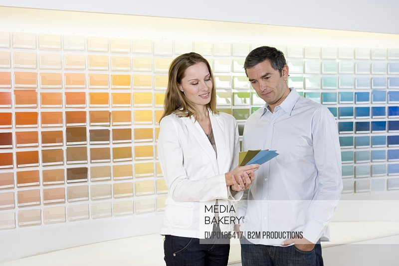Couple looking at color swatches in hardware shop