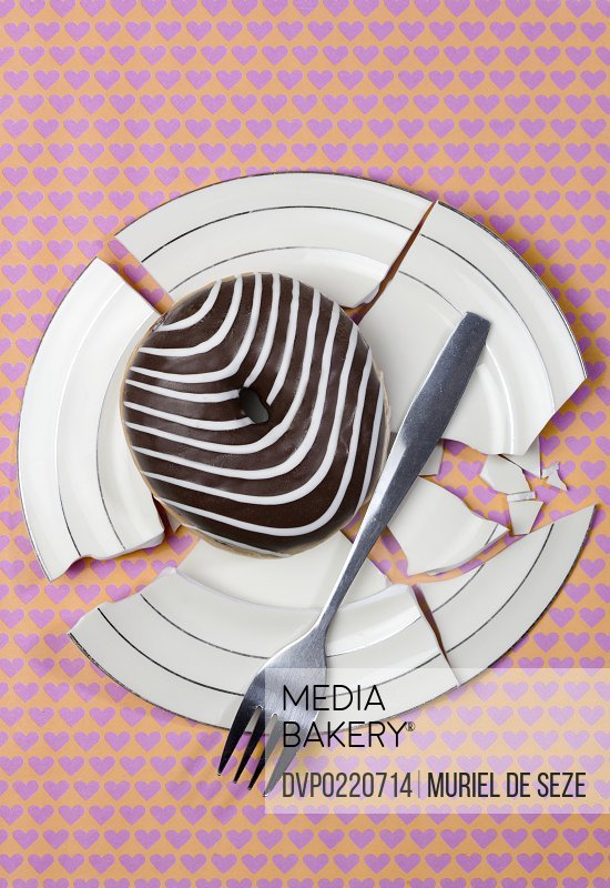 Chocolate donut with white stripes on broken plate.