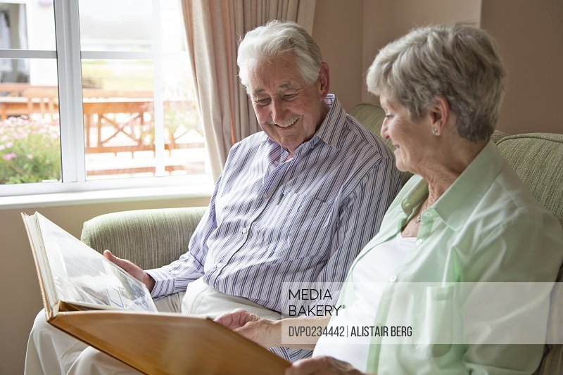 Elderly couple, aged 80-85, looking at a photo album together in a private retirement home