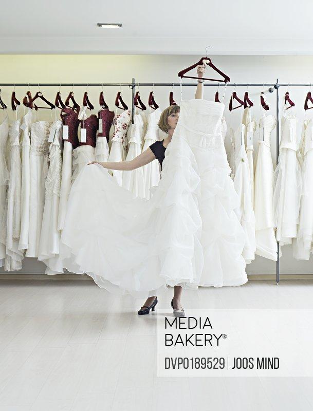Shop assistant showing wedding dress in shop