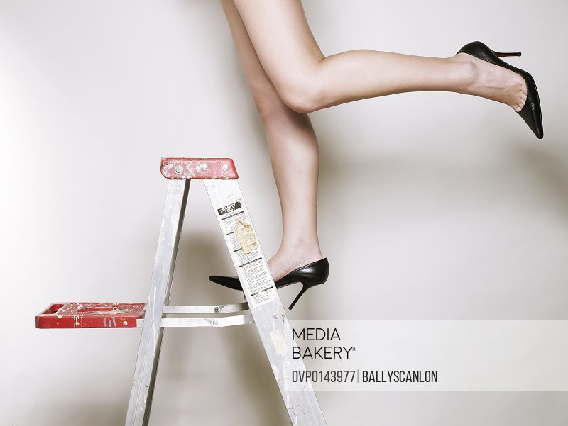 Young asian woman wearing high heels on a ladder
