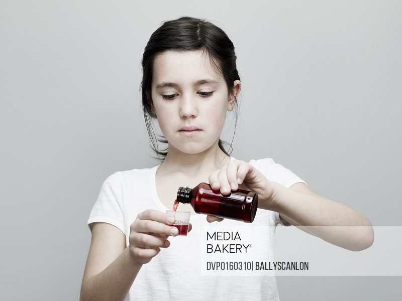 Young Girl Pouring Cough Medicine into Cup