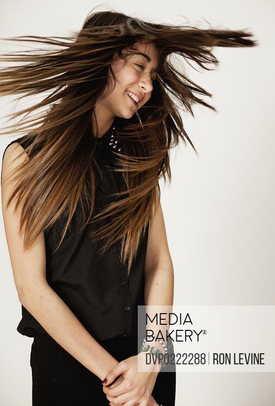 Teen girl flinging her long brown hair