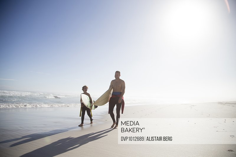 Father and son walking with surf boards on a beach