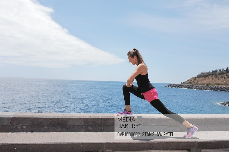 Woman stretching near ocean after jogging