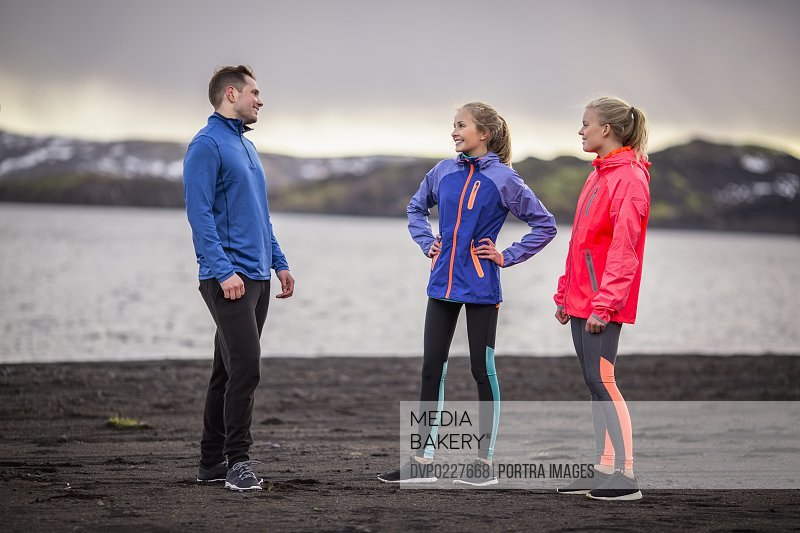 Full length of happy friends in neon sportswear communicating at lakeside