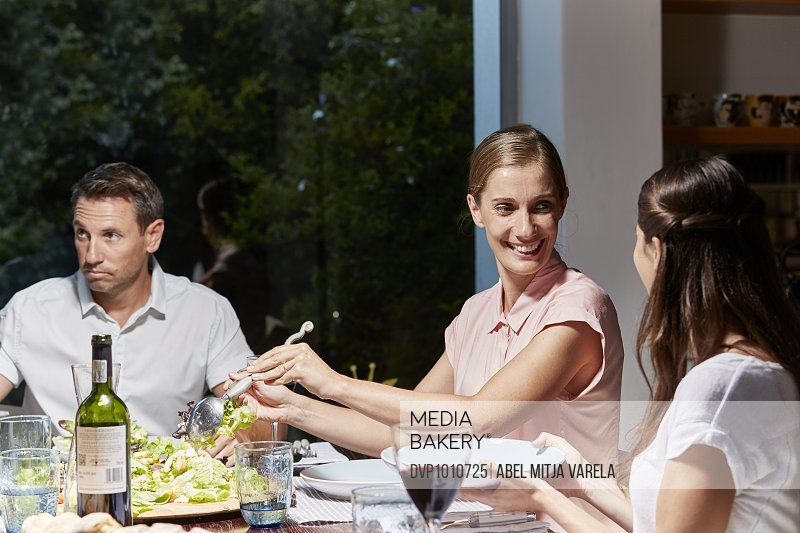 Woman serving food to friends at dinner table