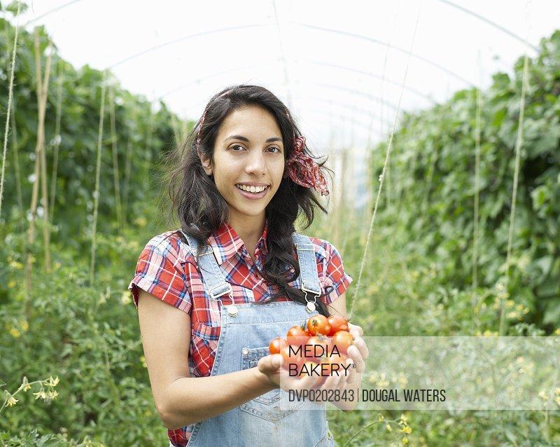 Asian woman holding fresh tomatoes.