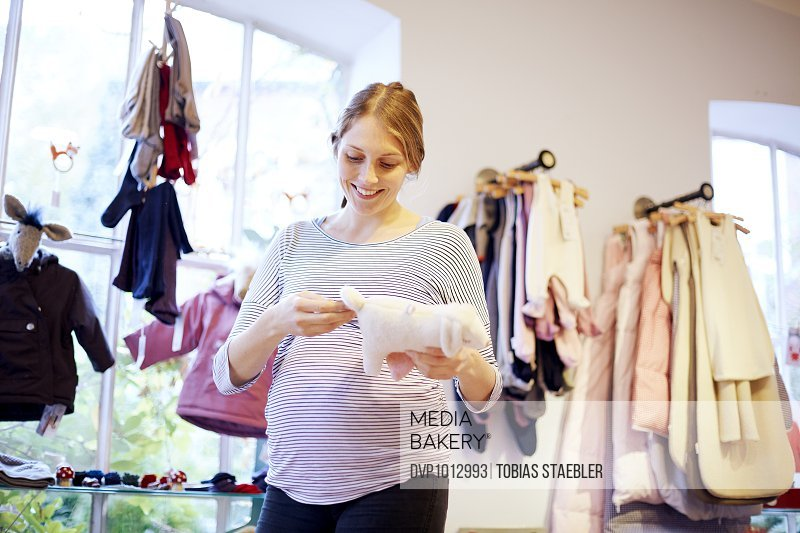 Pregnant woman in kids clothing shop
