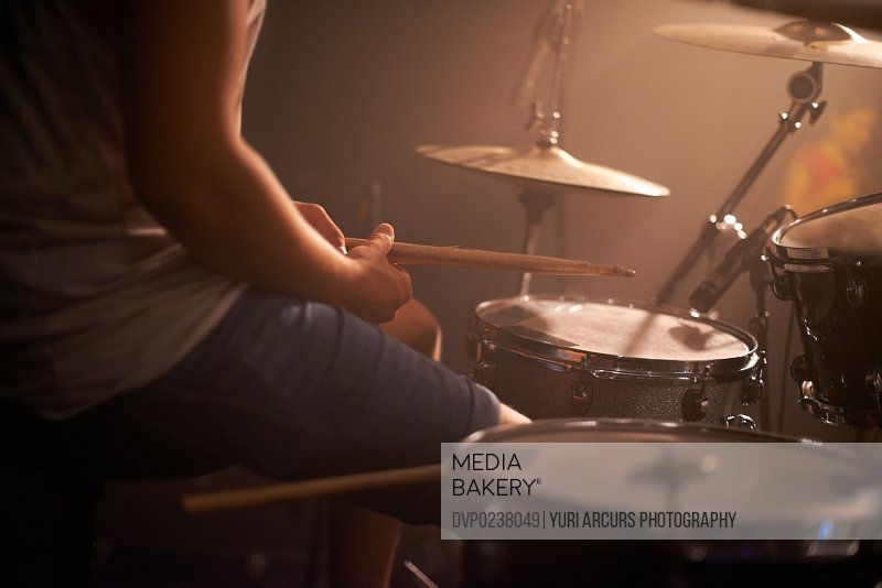 Cropped shot of a talented drummer hitting his drum skins hard at a gig. This concert was created for the sole purpose of this photo shoot, featuring 300 models and 3 live bands. All people in this shoot are model released.