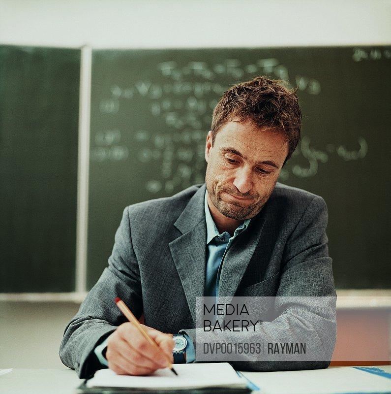 Tired Male Teacher Sitting Behind a Desk Working