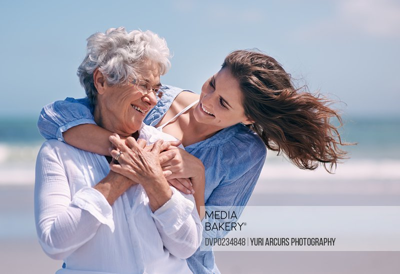 Shot of a beautiful young woman and her senior mother on the beach