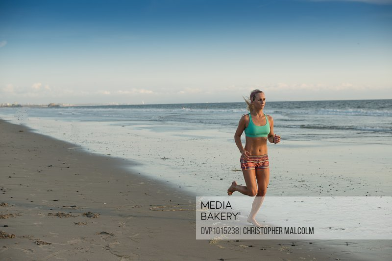 Woman goes for a run on the beach at sunset