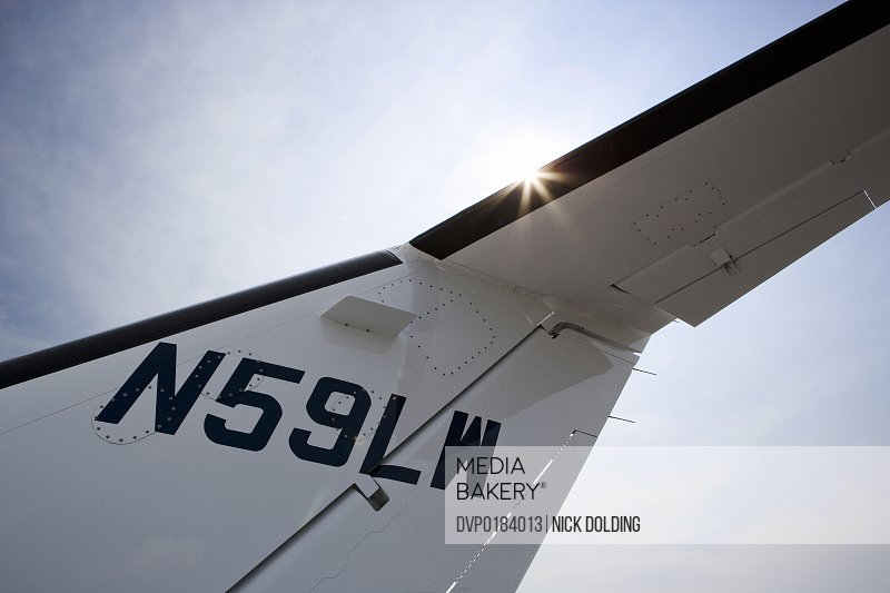 Detail of tailplane on private jet with sun flare