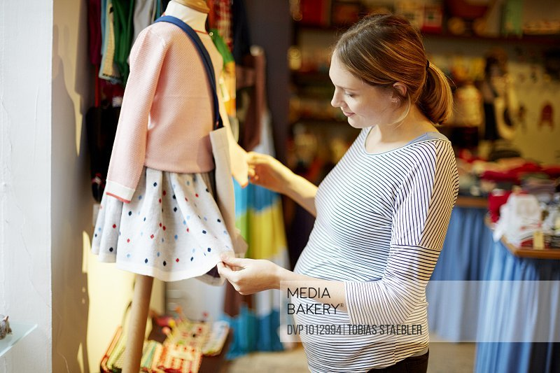 Pregnant woman looking at kids' clothes
