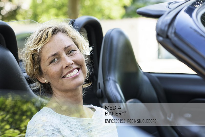 Woman sitting in open car smiling