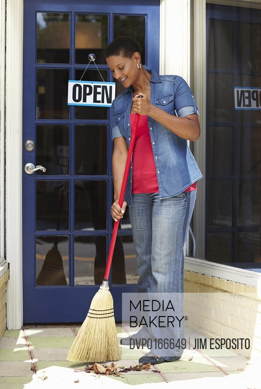 A small business owner sweeping the front of her store