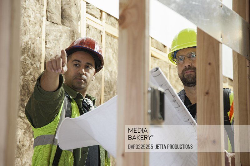 Two workers checking blue prints