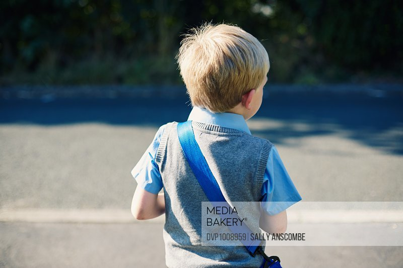 View from behind of school boy standing by a road waiting to cross, on his way to school