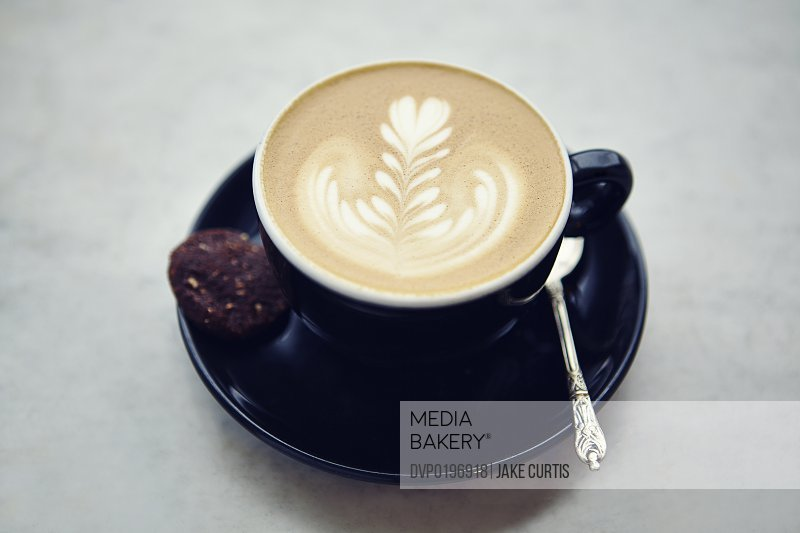 cup of coffee with leaf pattern froth and biscuit