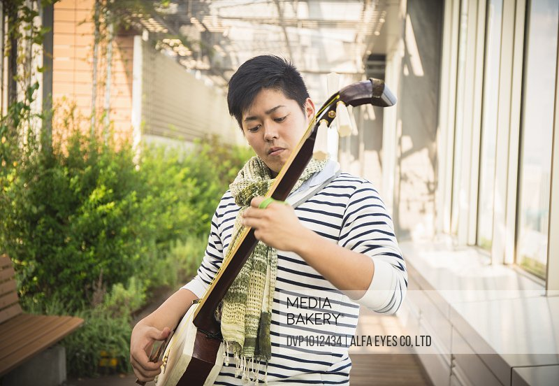Asian male playing the shamisen