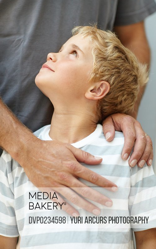 A cute young boy looking up to his father - close-up
