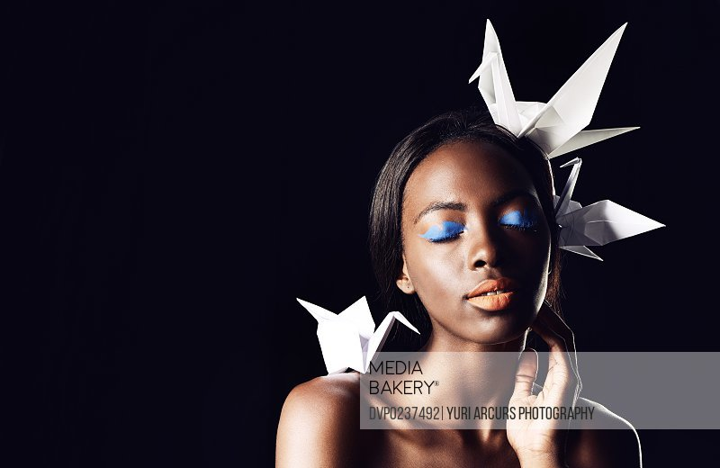 Cropped shot of a beautiful ethnic woman posing with origami birds on her head and shoulders