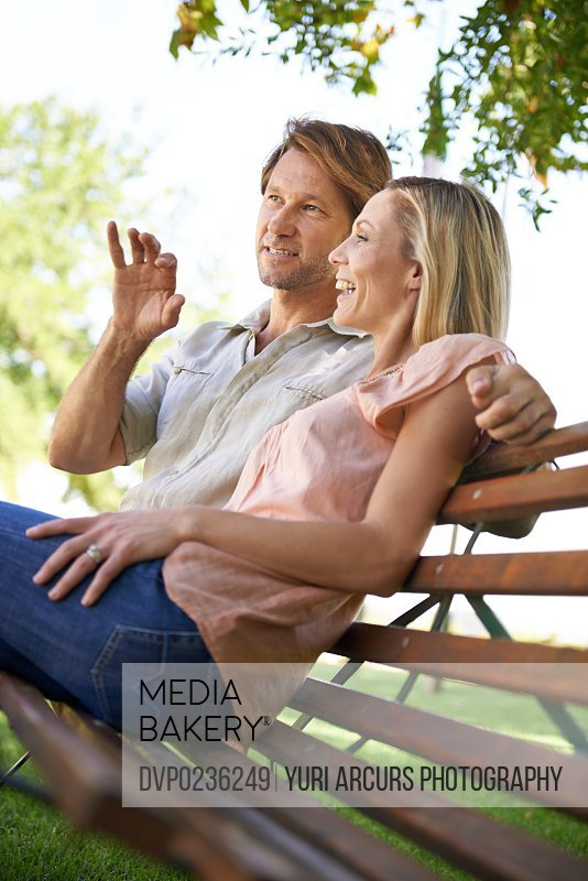 Shot of a happy mature couple sitting on a bench in the park