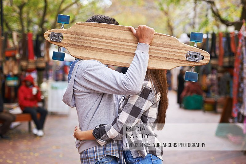 Fun shot of a young couple kissing behind a held up skate board