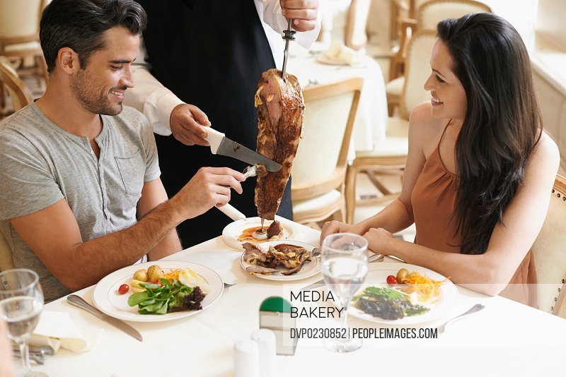 A waiter cutting meat off a skewer for a young couple at their table