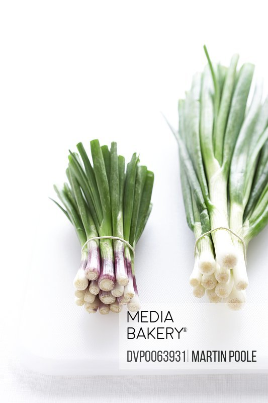 Two bunches of spring onions on white chopping board