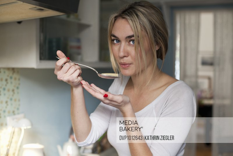 young woman cooking, testing pasta