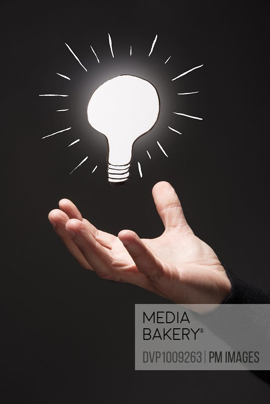 Man's hand open under brightly lit illustrated light bulb
