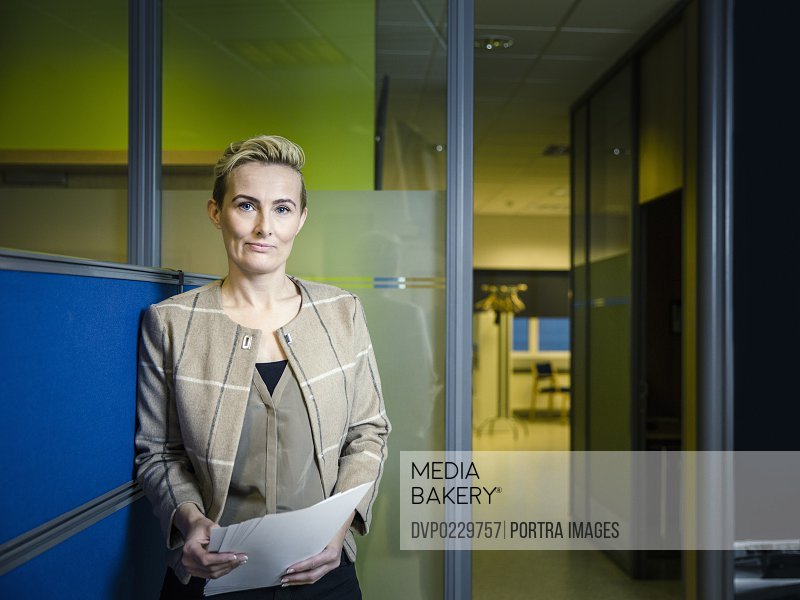 Confident businesswoman holding documents