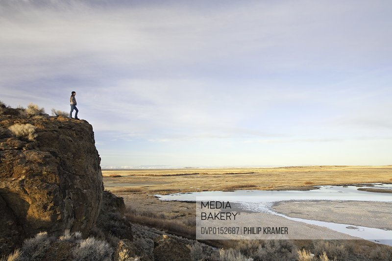 Woman stands on cliff overlooking nature preserve.