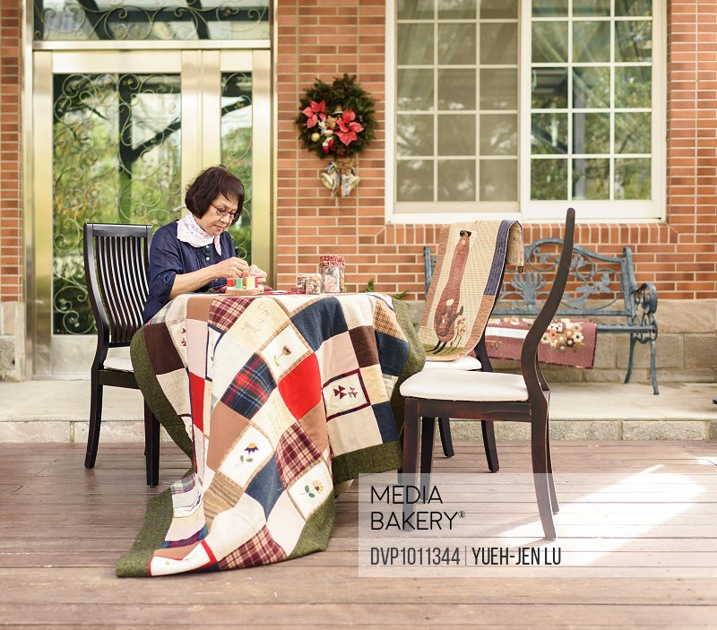 Elder woman sewing on porch