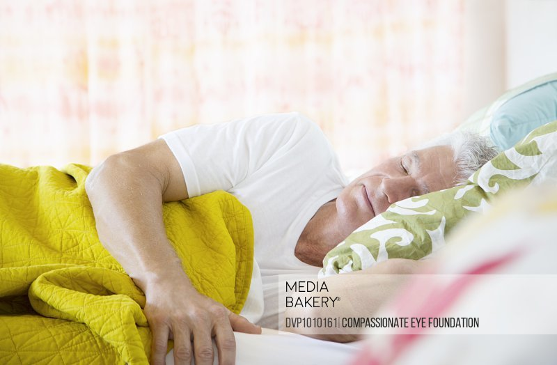Mature man sleeping in bed